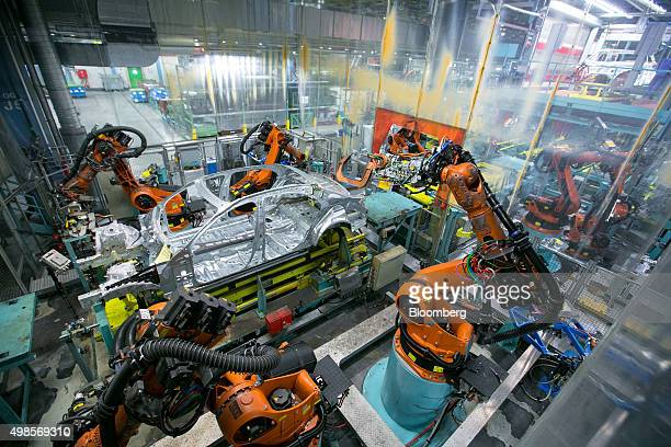 Robotic arms manufactured by Kuka AG operate on the body shell of a MercedesBenz SClass automobile on the assembly line at Daimler AG's MercedesBenz...
