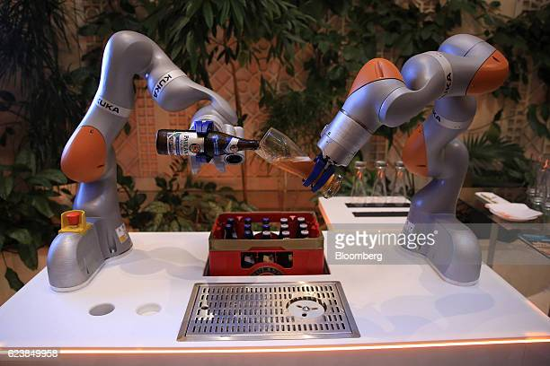 Robotic arms manufactured by Kuka AG pour a glass of Paulaner beer during the Sueddeutsche Zeitung Economic Summit in Berlin Germany on Thursday Nov...