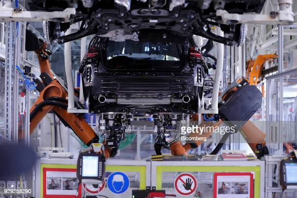 Robotic arms manufactured by Kuka AG secure the underbody panel to a Volkswagen AG Golf automobile on the production line at the VW factory in...