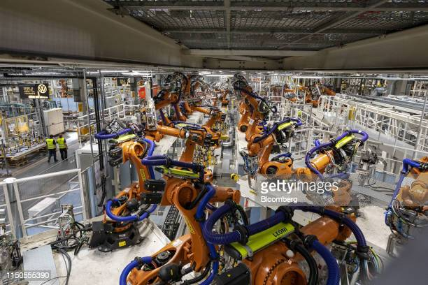 Robotic arms, manufactured by Kuka AG, sit on the production line for the all-electric ID. Car range at the Volkswagen AG automobile manufacturing...