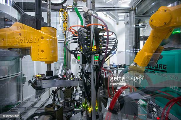 Robotic arms operate on the automobile gasoline direct injector valve assembly line at the Robert Bosch GmbH plant in Blaichach Germany on Tuesday...