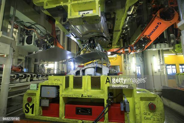 Robotic arms place steel sheets in a pressing machine inside the Volkswagen AG factory in Hanover Germany on Thursday April 12 2018 VW which has a...