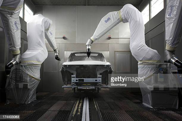 Robotic arms spray a Range Rover Sport automobile with a coat of white paint as the vehicle moves through the paint shop at the Jaguar Land Rover Plc...