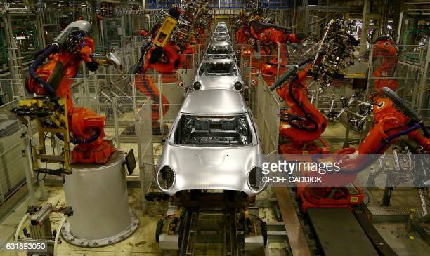 Robotic arms work on the bodyshells of Mini cars as they pass along a section of automated production line at the BMW Mini car production plant in...