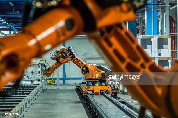 robotic arms working on assembly line - automated stock pictures, royalty-free photos & images