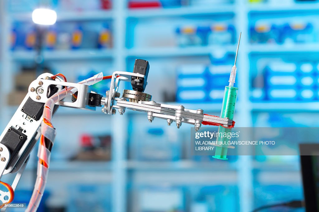 Robotic equipment holding syringe in lab : Stock Photo