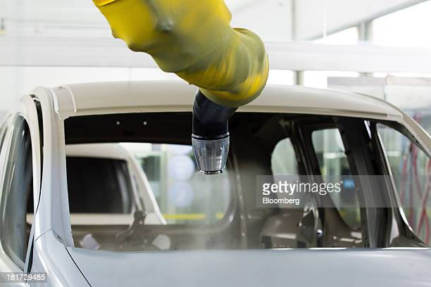A robotic painting machine sprays the hood of a Peugeot Partner automobile in the paintshop at the PSA Peugeot Citroen production plant in Mangualde...