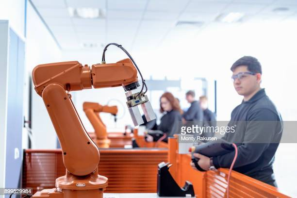 robotics apprentice with robot in robotics facility - training course stockfoto's en -beelden