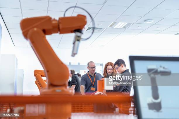 robotics apprentices using test industrial robots in robotics facility - robotic arm stock pictures, royalty-free photos & images