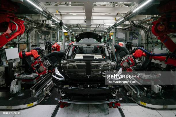 Robotics arms install the front seats to the Tesla Model 3 at the Tesla factory in Fremont California on Thursday July 26 2018