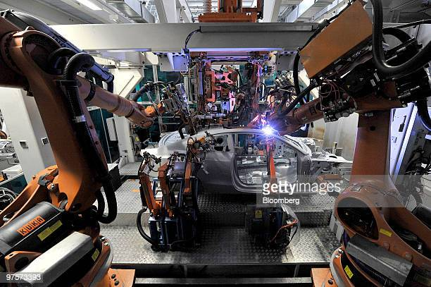 KUKA robotics arms work on an Audi A5 automobile during the assembly process at the Audi AG factory in Ingolstadt Germany on Monday March 8 2010...