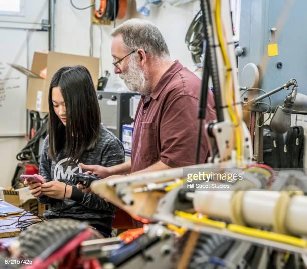 Robotics student and teacher examining machinery