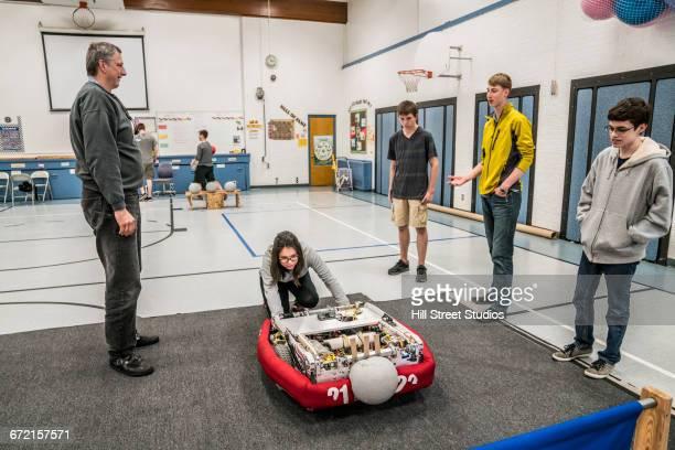 Robotics students and teacher examining robot
