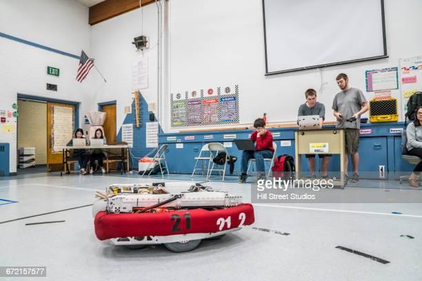 Robotics students with robot in gymnasium