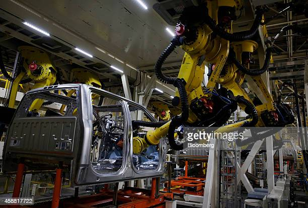 Robots assemble a 2015 Ford Motor Co F150 truck on the production line at the company's Dearborn Truck Assembly facility in Dearborn Michigan US on...