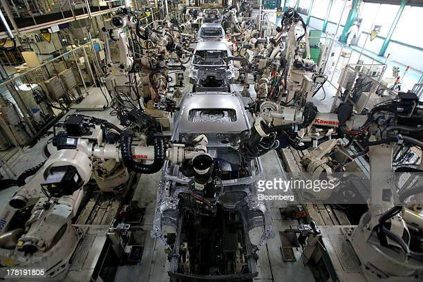 Robots assemble Mazda Motor Corp Atenza sedans on the production line at the company's plant in Hofu Yamaguchi Prefecture Japan on Tuesday Aug 27...
