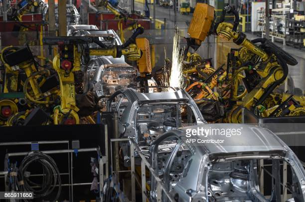 Robots assemble vehicle frames at the assembly line at the French auto maker PSA Peugeot Citroen factory on October 10 in Mulhouse The PSA plant in...