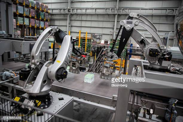 Robots bundle bottles of CocaCola Co brand water move along a conveyor at the CocaCola Cambodia Bottling Plant operated by Cambodia Beverage Co which...