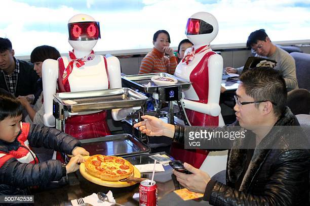 Robots deliver meals for customers at a restaurant on December 10 2015 in Suzhou China The restaurant has four robots delivering meals one robot...
