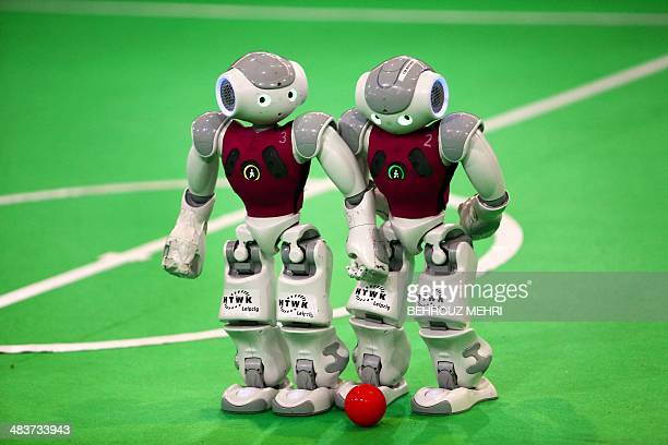 Robots from German NaoTeam HTWK of the Leipzig University of Applied Sciences take part in a football game against 'Dutch Nao Team' from the Van...