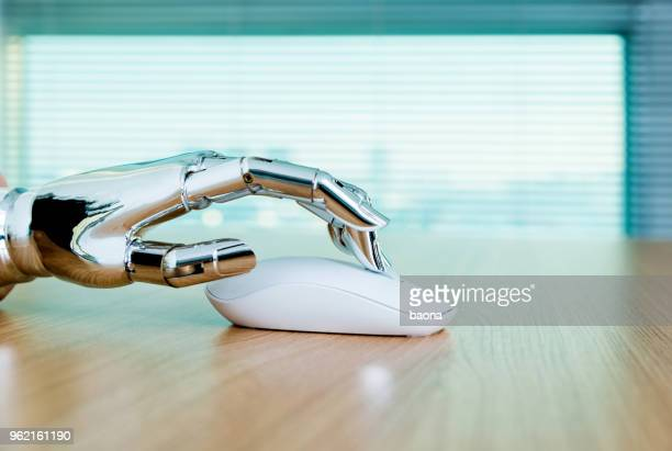 robot's hand using computer mouse - automation stock pictures, royalty-free photos & images
