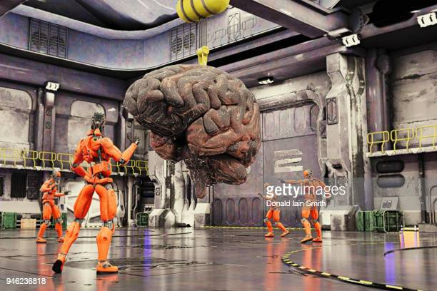 Robots in hangar manoeuvring giant brain on crane