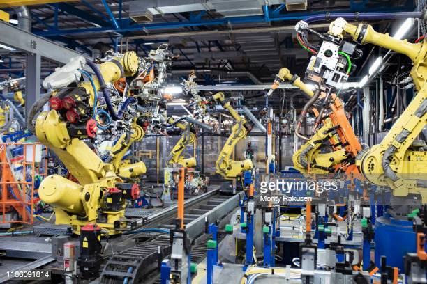 robots on production line in car factory - factory stock pictures, royalty-free photos & images