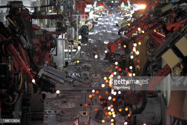 Robots perform welds on the production line of the Hyundai Motor Co. Ulsan factory in Ulsan, South Korea, on Monday, Dec. 19, 2011. Hyundai Motor...
