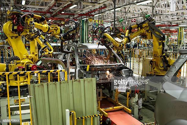 Robots weld the frame of a Mahindra Mahindra Ltd XUV 500 sportutility vehicle on the production line at the company's facility in Chakan Maharashtra...