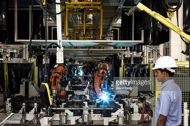 Robots weld the frame of an Eicher Polaris Pvt Multix personal utility vehicle at the company's factory in Jaipur Rajasthan India on Thursday June 18...