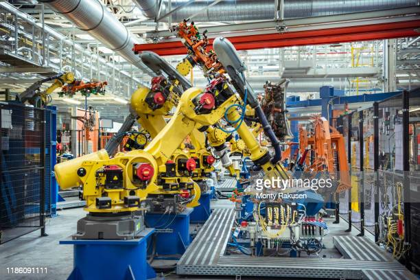 robots with car parts in car factory - factory stock pictures, royalty-free photos & images