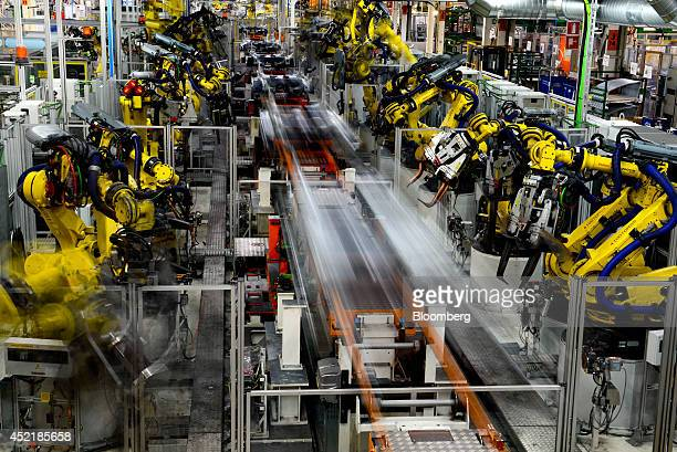 Robots work on Seat Leon vehicles on the production line during assembly at Volkswagen AG's Seat automobile plant in Martorell Spain on Tuesday July...