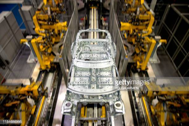 Robots work on the MINI production line at the BMW group plant in Cowley, near Oxford on July 9, 2019.