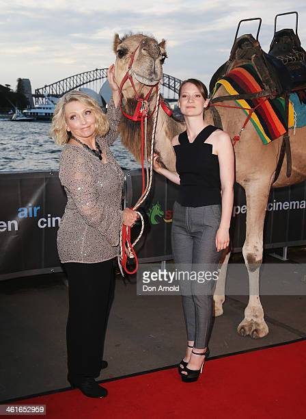 Robyn Davidson and Mia Wasikowska pose alongside a camel at the St George Openair Cinema Tracks premiere on January 10 2014 in Sydney Australia