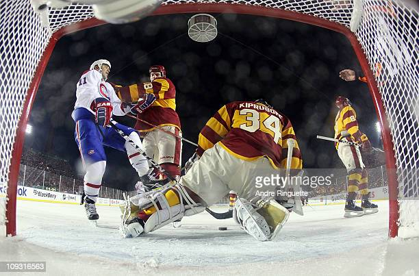 Robyn Regehr and goaltender Miikka Kiprusoff of the Calgary Flames combine to stop Scott Gomez of the Montreal Canadiens during the 2011 NHL Heritage...