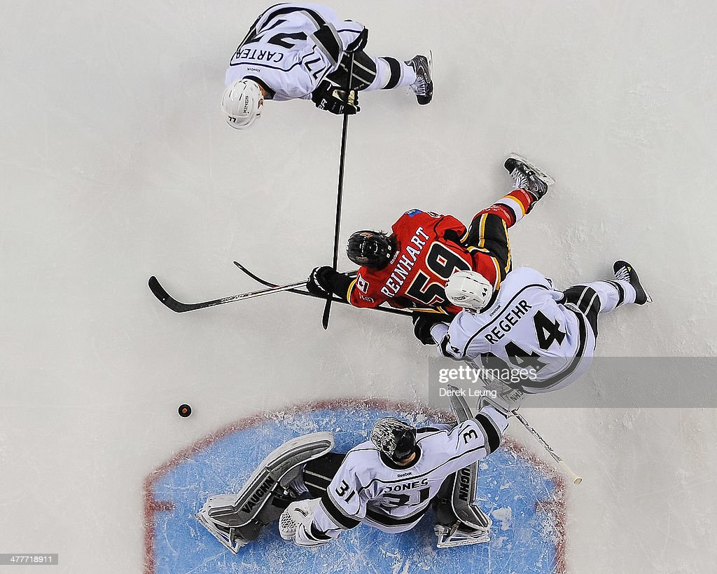 Robyn Regehr #44 and Martin Jones #31 of the Los Angeles Kings defend net against Max Reinhart #59 of the Calgary Flames during an NHL game at Scotiabank Saddledome on March 10, 2014 in Calgary, Alberta, Canada. The Kings defeated the Flames 3-2.