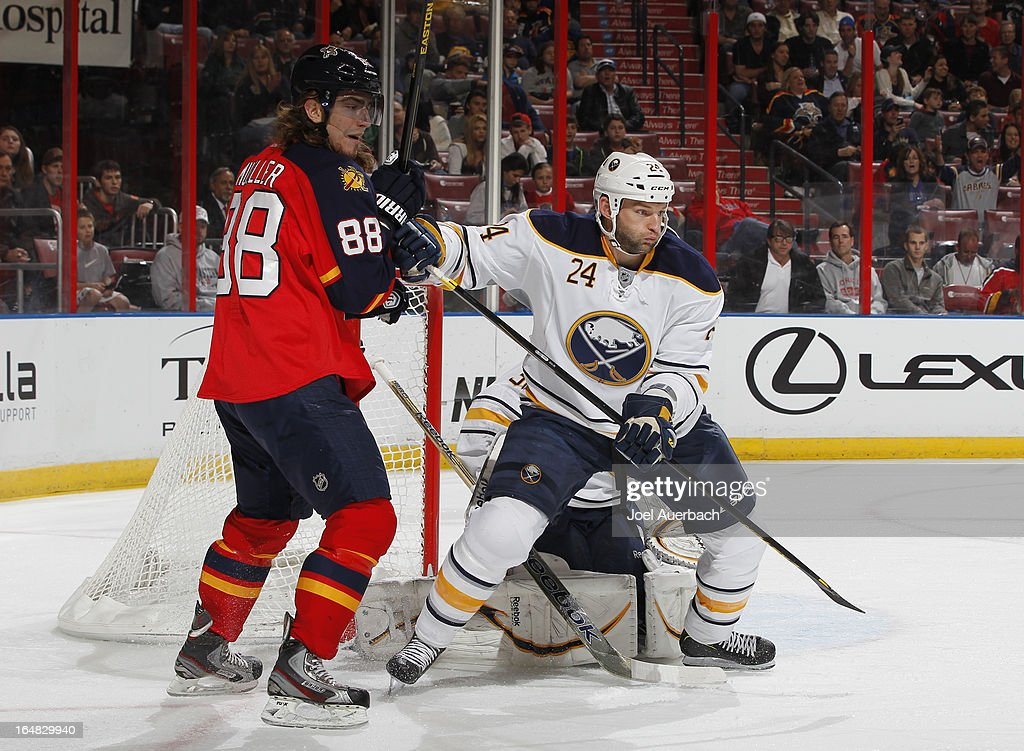 Robyn Regehr #24 assists goaltender Ryan Miller #30 of the Buffalo Sabres defend the net with Peter Mueller #88 of the Florida Panthers waiting at the post at the BB&T Center on March 28, 2013 in Sunrise, Florida.