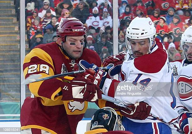 Robyn Regehr of the Calgary Flames and Brian Gionta of the Montreal Canadiens battle during the 2011 NHL Heritage Classic Game at McMahon Stadium on...