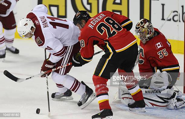 Robyn Regehr of the Calgary Flames battles for the puck with Martin Hanzal of the Phoenix Coyotes in front of goalie Henrik Karlsson of the Flames in...