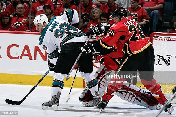 Robyn Regehr of the Calgary Flames pushes Ryan Clowe of the San Jose Sharks during game six of the 2008 NHL Stanley Cup Playoffs conference...