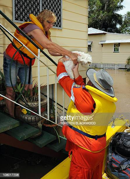 Robyn Russell hands her dog 'Elle' to emergency personnel before being evacuated from her floodbound home in Rockhampton on January 6 2011 Tens of...