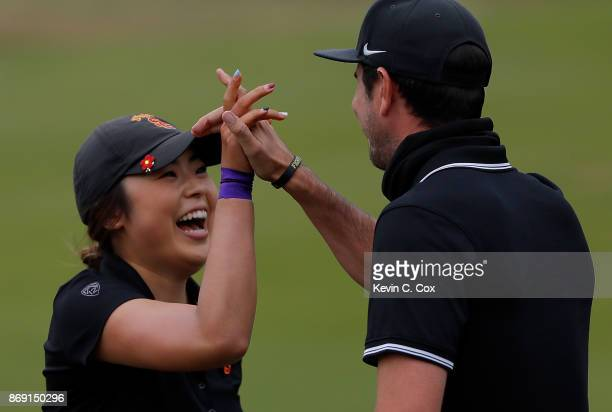 Robynn Ree of the USC Trojans reacts after defeating Shannon Aubert of the Stanford Cardinal on the 18th green wit assistant coach Steward Burke...