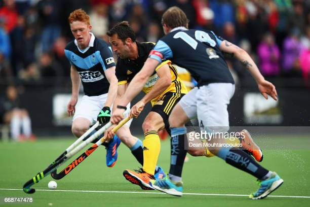 Roc Oliva of Atletic Terrassa HC battles for the ball with Ryan Getty and Daniel Buser of Lisnagarvey during the Euro Hockey League KO16 match...