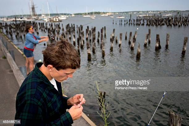 Rocco DiDonato of Portland ties a hook to his fishing line as his girlfriend Janessa Napolitano also of Portland casts her line into Casco Bay as the...