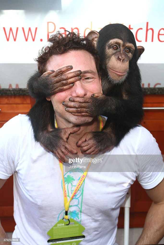 Rocco DiSpirito poses with a monkey during the Fun And Fit As A Family Sponsored By Carnival Featuring Goya Kidz Kitchen Hosted By Robert Irvine during the Food Network South Beach Wine & Food Festival at Jungle Island on February 22, 2014 in Miami, Florida.
