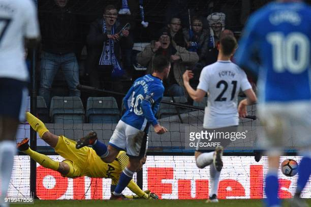 Rochdale's English striker Ian Henderson scores the opening goal past Tottenham Hotspur's Dutch goalkeeper Michel Vorm during the English FA Cup...