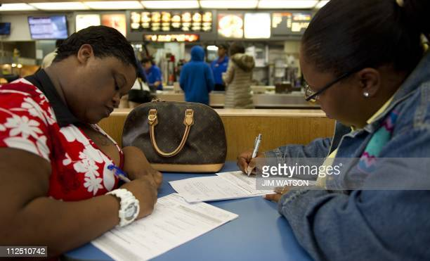 Rochelle Maddox and Rosalind Emyimah fill out an application as they apply for a crew position at McDonalds in Washington DC April 19 2011 McDonald's...