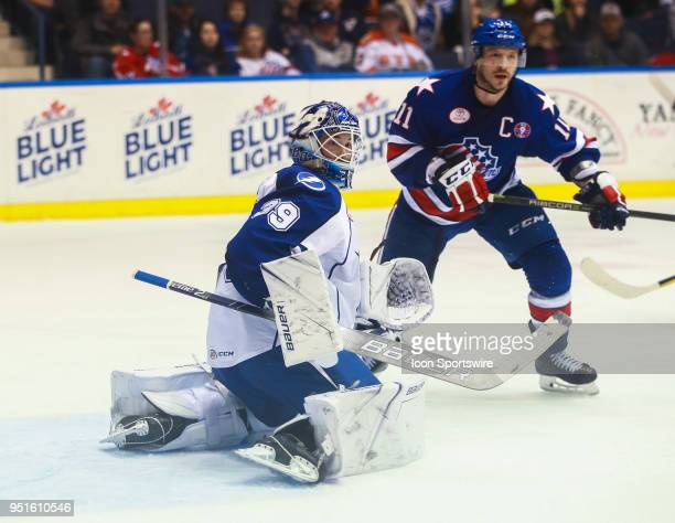 Rochester Americans center Kevin Porter and Syracuse Crunch goaltender Connor Ingram look for a rebound during an AHL game between the Syracuse...