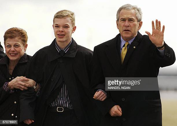 US President George W Bush waves as he walks towards the media with Jason McElwain and his mother Debbie McElwain upon arrival 14 March 2006 at...