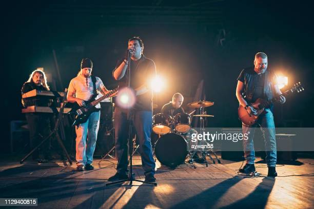 rock and roll band performing hard rock music on stage - performance group stock pictures, royalty-free photos & images